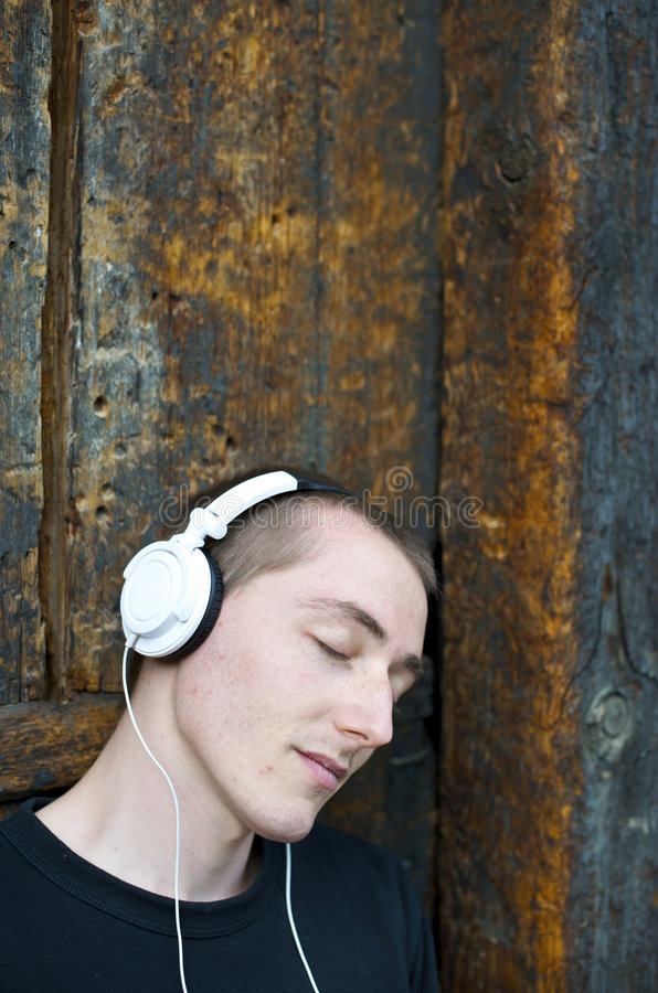 Listen to the music. Man listening to the music in a park with white headphones stock photo