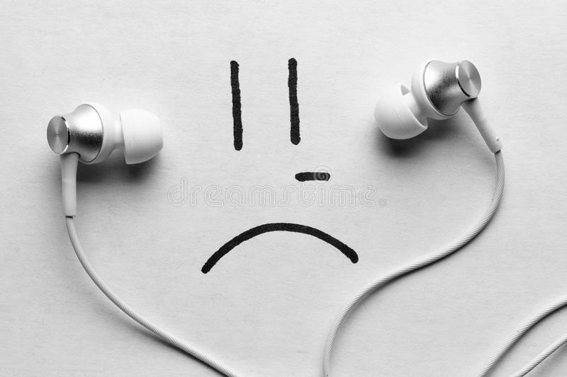 Listen to sad music concept. Headphones and sad smile royalty free stock photography