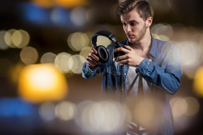 Listen to the silence. Young modern style handsome man take off his music headphones to hear the silence or different sound. Dynamic background - abstract stock image