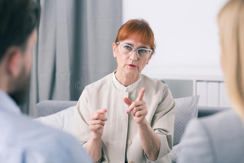 Listen, you can't fight with each other. Mature marriage counselor and her patients royalty free stock photos