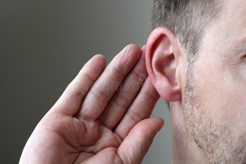 Listening. Close up on hand and ear listening for a quiet sound or paying attention stock images