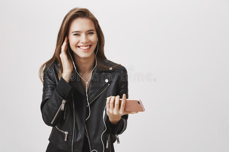 Listening audiobook of her favorite author. Portrait of attractive successful businesswoman in leather jacket, holding royalty free stock images
