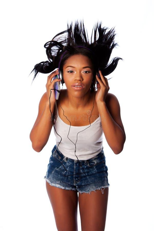 Listening jamming to music. Beautiful teenager jamming listening to music with wild hair, on white stock photo