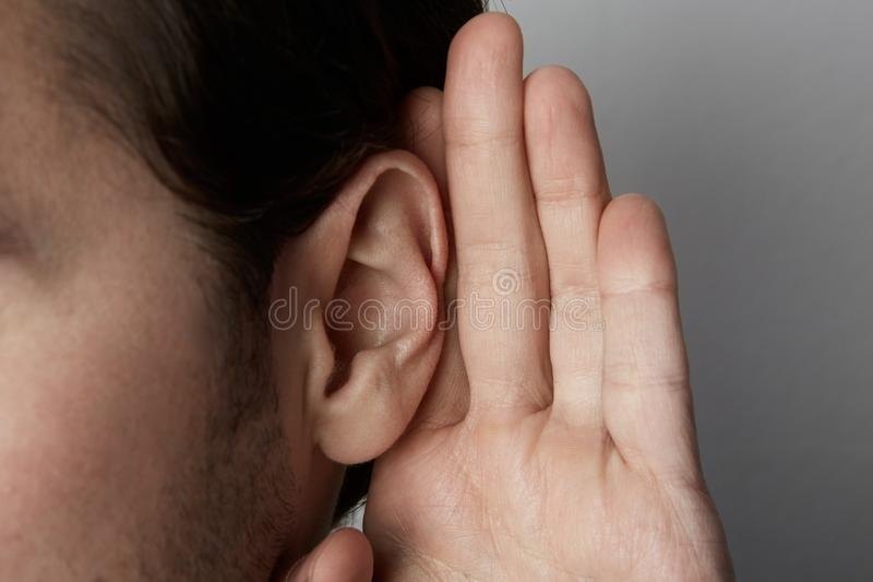 Listening male holds his hand near his ear over grey background.Closeup. royalty free stock image