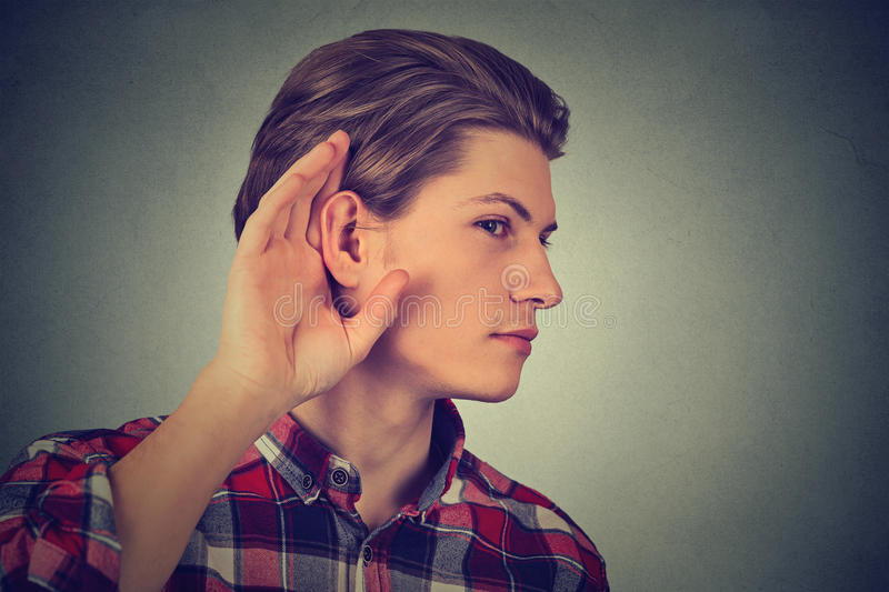 Listening man holds with hand to ear gesture. Listening man holds his hand near ear royalty free stock images