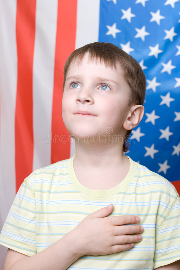 Listening national anthem. A boy listening national anthem on 4th of July stock photography