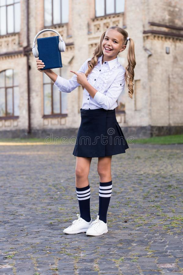 Listening school book. Knowledge assimilate better this way. Audio book concept. Digital technologies for learning. Elearning and modern methods. Girl cute stock image