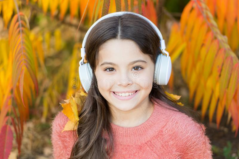 Listening song. Enjoy music outdoors fall warm day. Audio file. Educational podcast. Autumn playlist concept. Feel joy. Kid girl relaxing near autumn tree with stock image