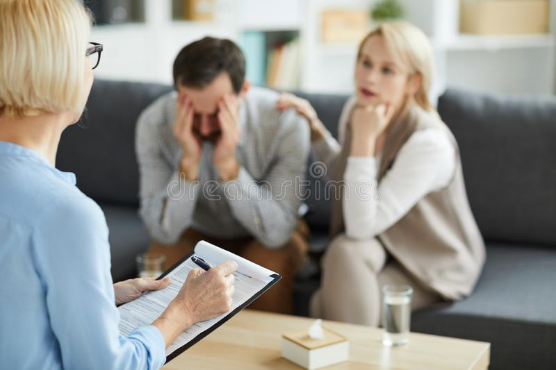 Listening to couple. Mature professional counselor making notes in document while listening to young women sitting next to troubled husband royalty free stock image