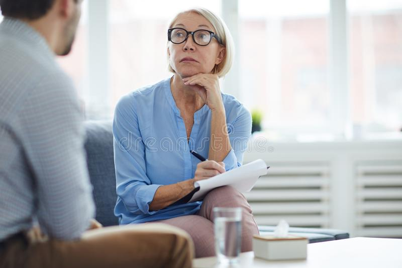 Listening to explanation of problem. Serious blonde mature counselor in eyeglasses listening to patient telling his story and explaining the problem stock photo
