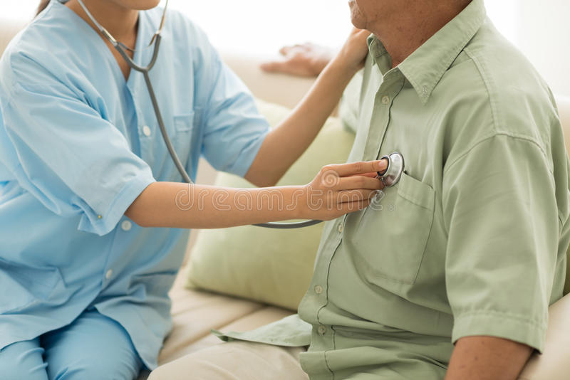 Listening to heartbeat. Doctor listening to heartbeat of senior patient at home royalty free stock images