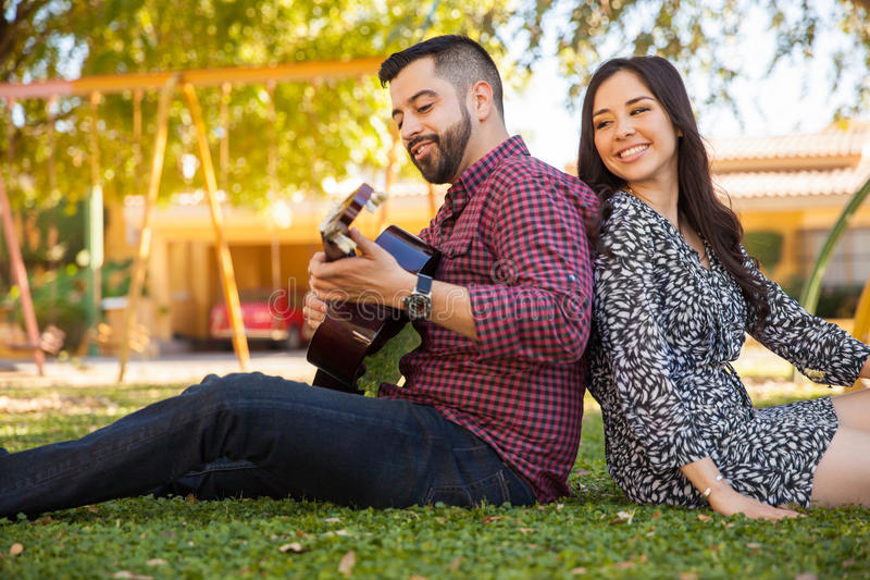Listening to my boyfriend play. Beautiful young women enjoying the music her boyfriend plays in the guitar royalty free stock photo