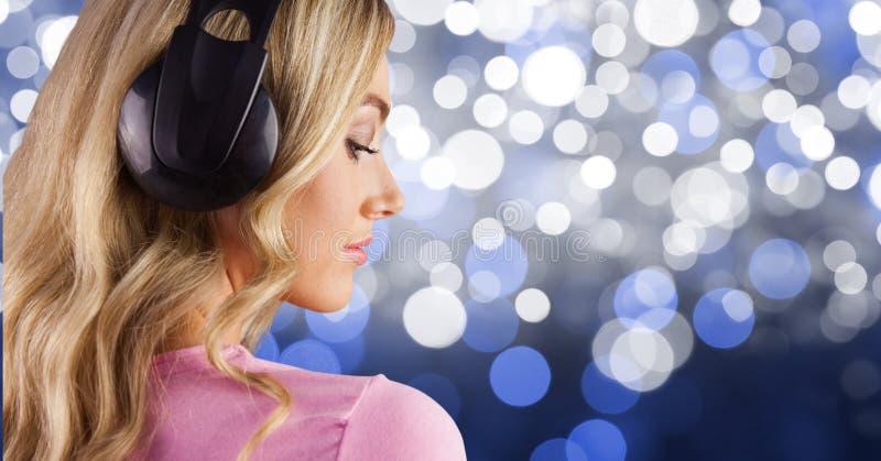 listenning musik för Blond-hår flicka med hörlurar tillbaka till fotoet med blå bakgrund royaltyfri fotografi