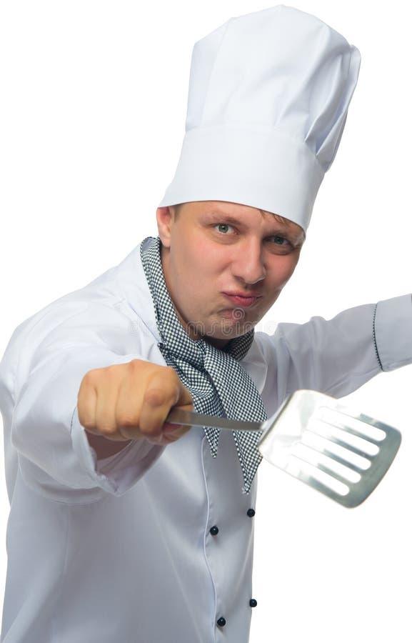 Listig kock, håll en apparat i hans hand, att vända kotletterna arkivbilder