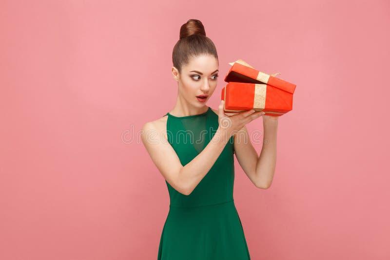 Listig kvinna som unboxing den röda gåvaasken som inom ser royaltyfri foto