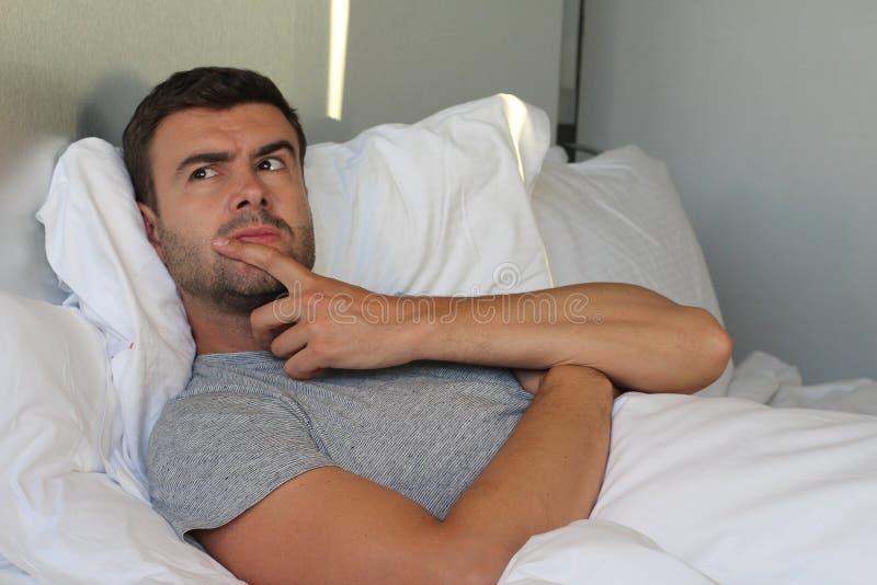Listig man som konspirerar en hämnd i säng royaltyfria bilder