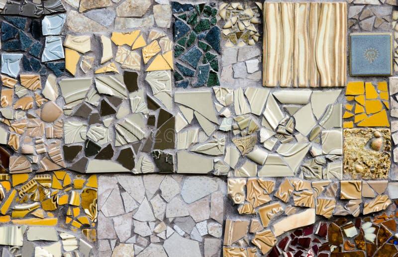 Listig mozaïekontwerp van geassorteerde gebroken tegel aan de kant van een gebouw stock foto