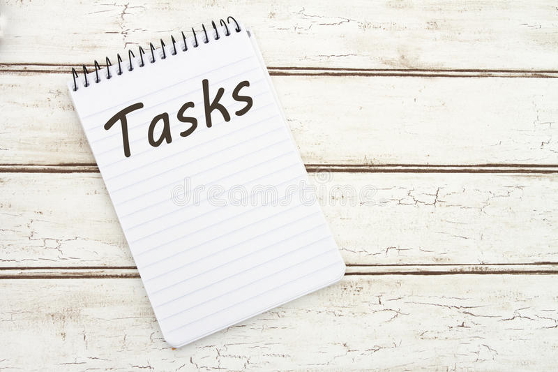 Listing Your Tasks. A spiral Notepad that has the word Tasks over a distressed wood background royalty free stock photography