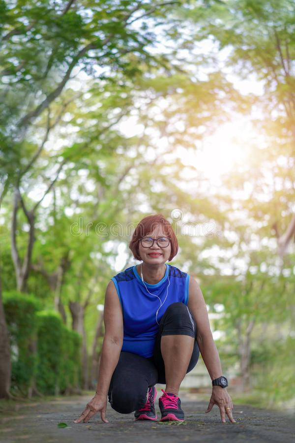 Listo feliz de la mujer asiática mayor para comenzar a correr activar en el parque foto de archivo