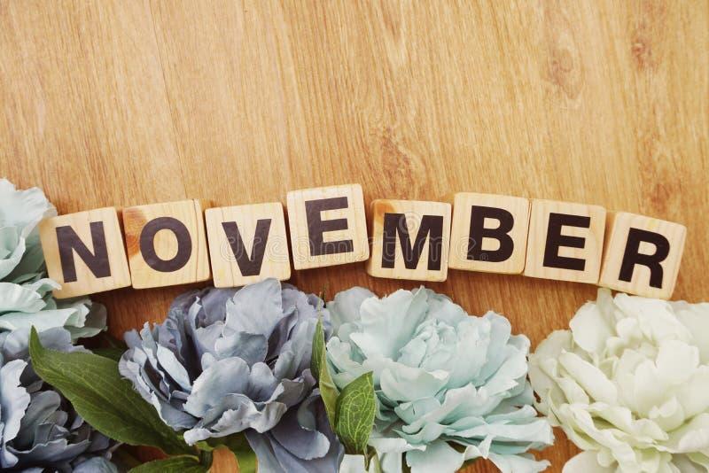 Listopadu abecadła listu drewniany sześcian z przestrzeni kopią na drewnianej tła i kwiatu dekoraci obrazy stock