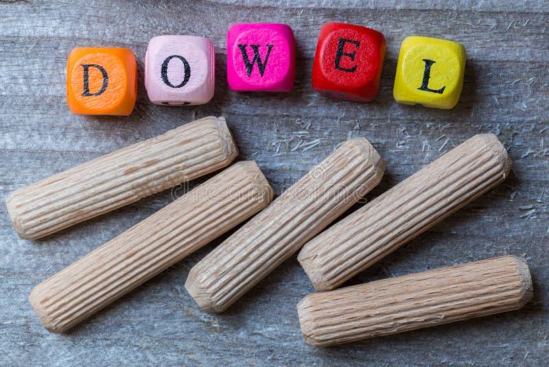 Listowi sześciany i dowels na szarym drewnianym unaocznieniu zdjęcia stock