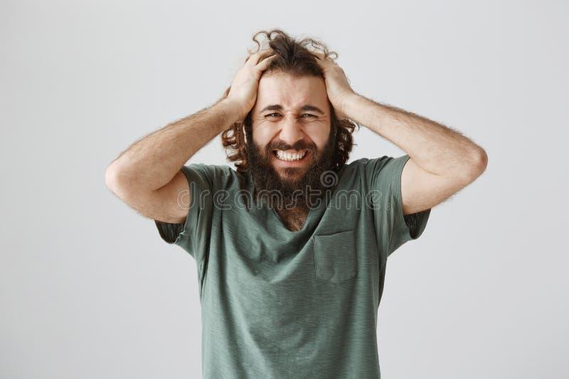 Listra preta na vida começada Tiro interno do homem oriental devastado incomodado com a barba que guarda Hans na cabeça e que faz fotografia de stock