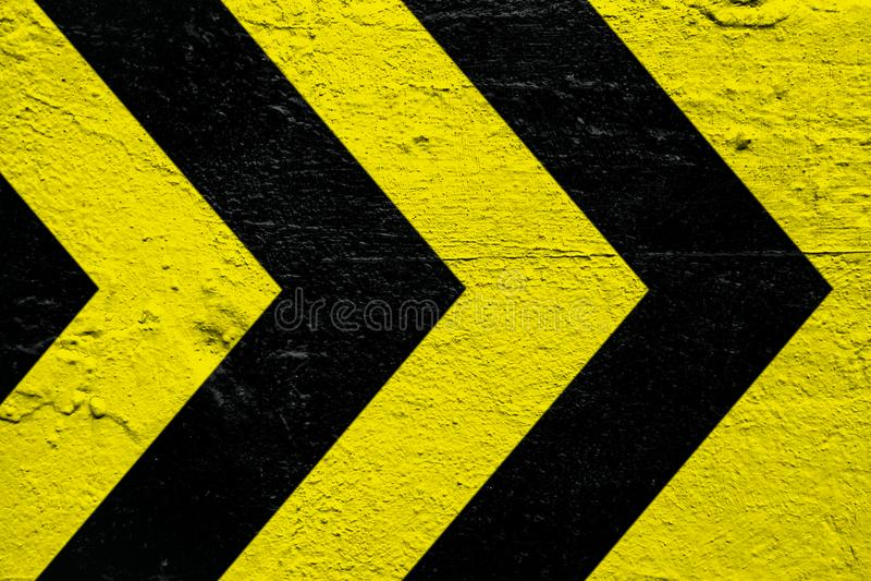 Listras amarelas e pretas do sinal de advertência do perigo como as setas pintadas sobre o cimento concreto muram como o fundo da imagem de stock