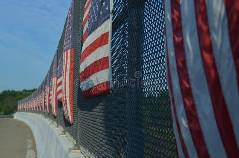 Listras verticais de bandeiras americanas no lado ensolarado da cerca da passagem superior da estrada foto de stock
