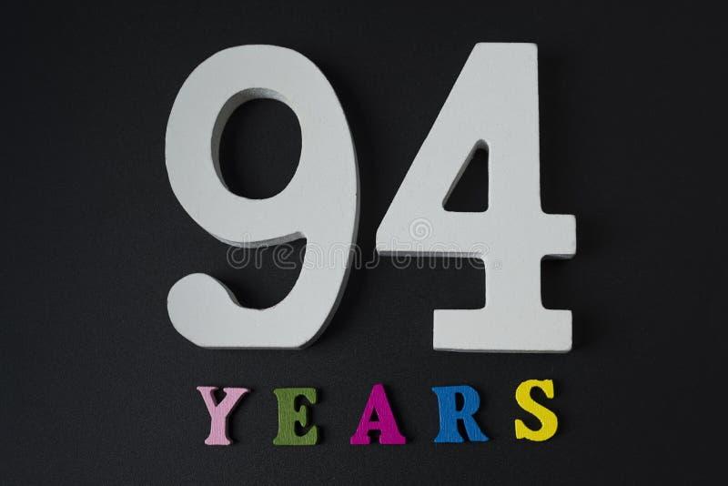 Listy i liczby dziewięćdziesiąt cztery roku na czarnym tle fotografia stock