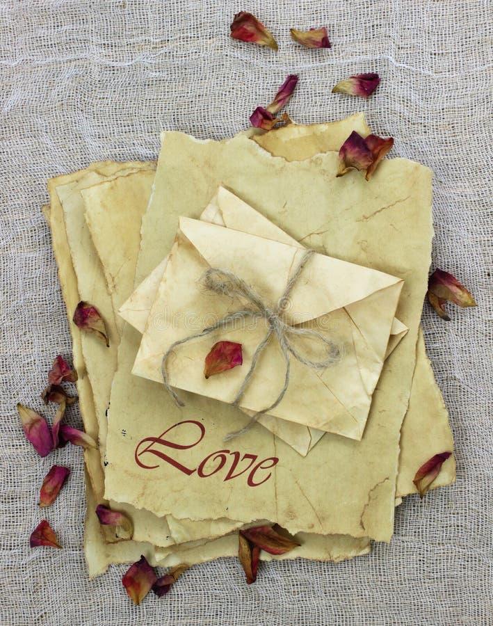 Listy miłośni i koperty robić antykwarski pergaminowy papier z wysuszonymi różanymi płatkami zdjęcie stock
