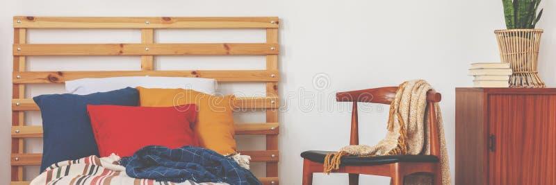 Lit avec le bleu, le carmin et les oreillers ocres placés dans l'intérieur blanc de chambre à coucher photos stock