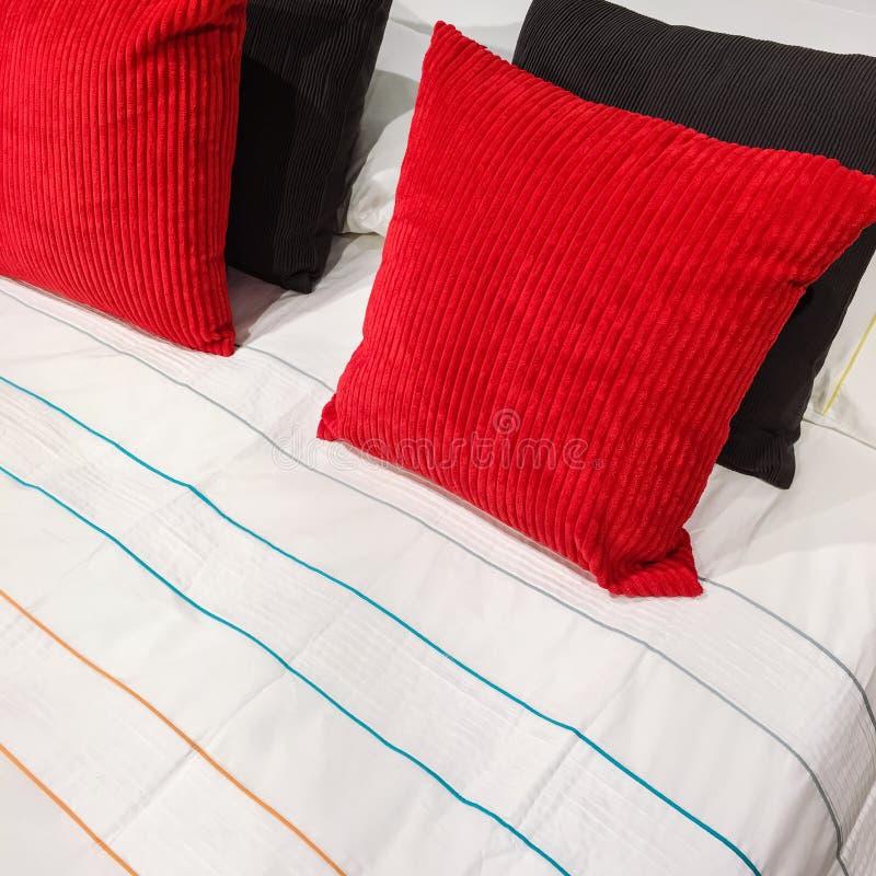 Lit avec les coussins rouges et noirs de velventine photos stock