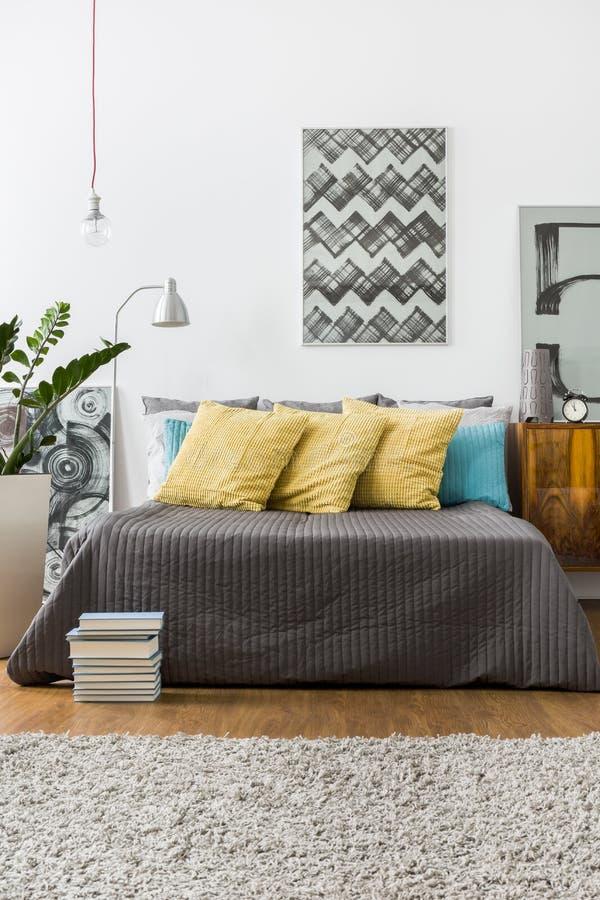 Lit avec les oreillers jaunes décoratifs photographie stock
