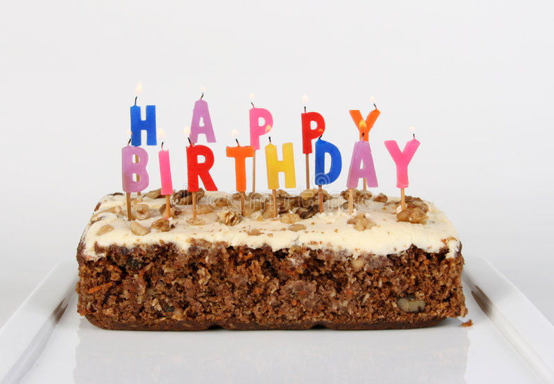 Lit Birthday Cake. Birthday cake candles lit on a carrot cake royalty free stock photo