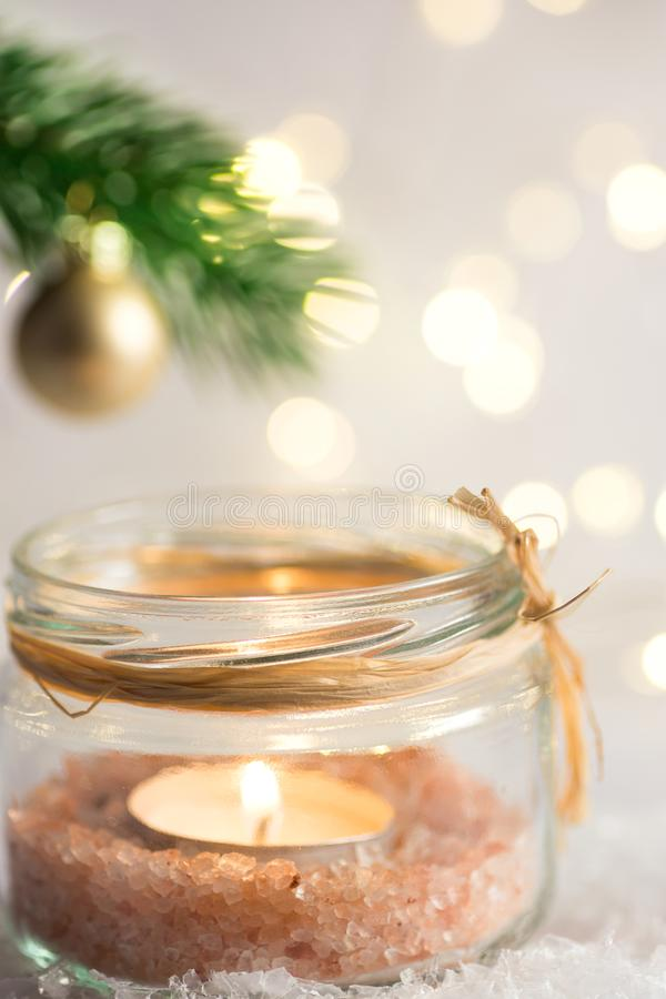 Lit candle in crystal jar candleholder hanging Christmas tree branch with golden ball. Snow winter forest. Lights. New Year royalty free stock photography