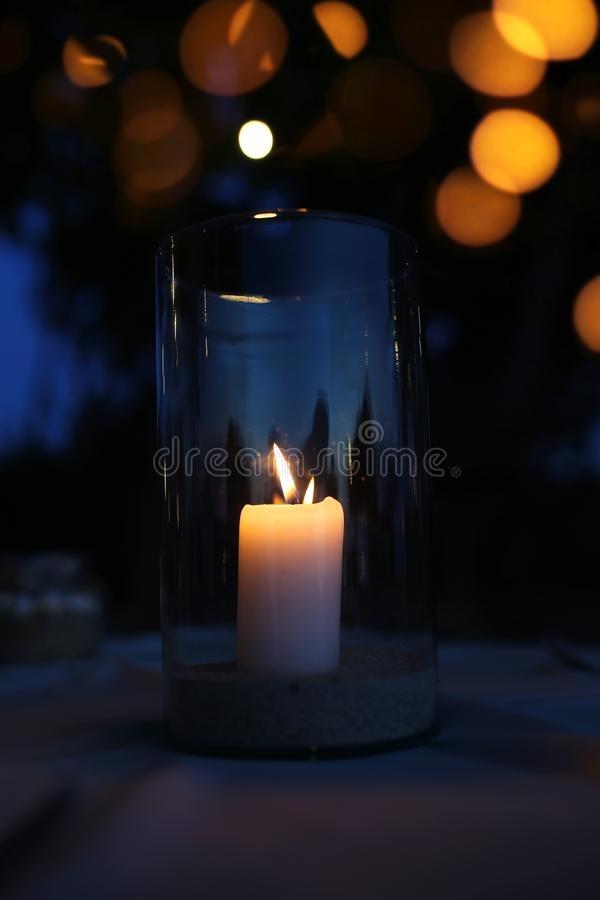 A lit candle in a glass candlestick, standing late at night on a table in a cafe stock image