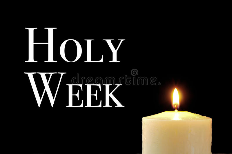 A lit candle and the text holy week. Written in white on a black background royalty free stock photos