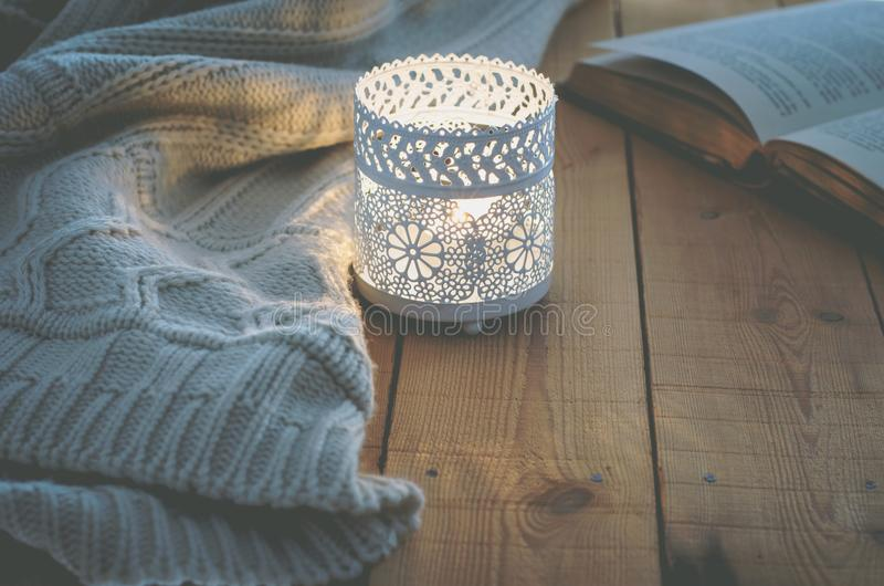 Lit Candle White Knitted Sweater Open Book on Plank Wood Table by Window. Cozy Winter Autumn Evening. Natural Light stock images