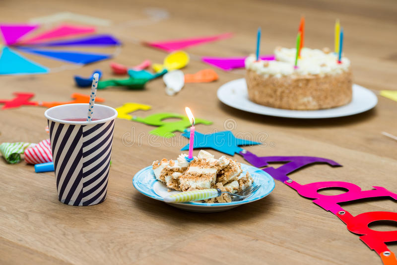 Lit Candles On Birthday Cake At Table stock photo