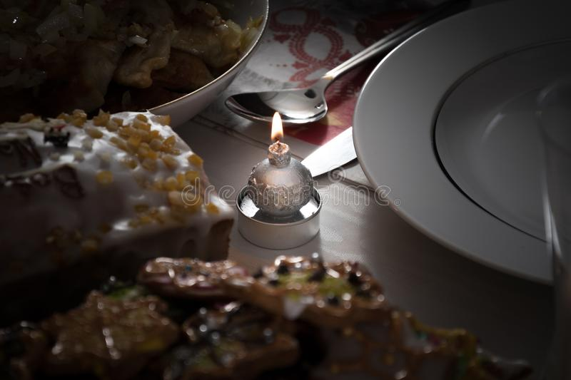 A lit christmas candle on a table next to frosted colorful cookies and a glazed cake with orange peel. stock photography