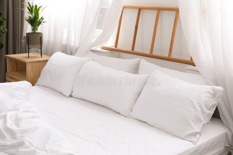Lit confortable avec les oreillers mous dans la chambre image stock