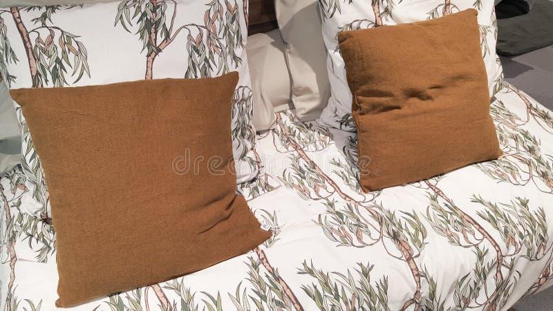 Lit confortable de détail intérieur clair lumineux de chambre à coucher avec les fleurs de toile blanches images stock