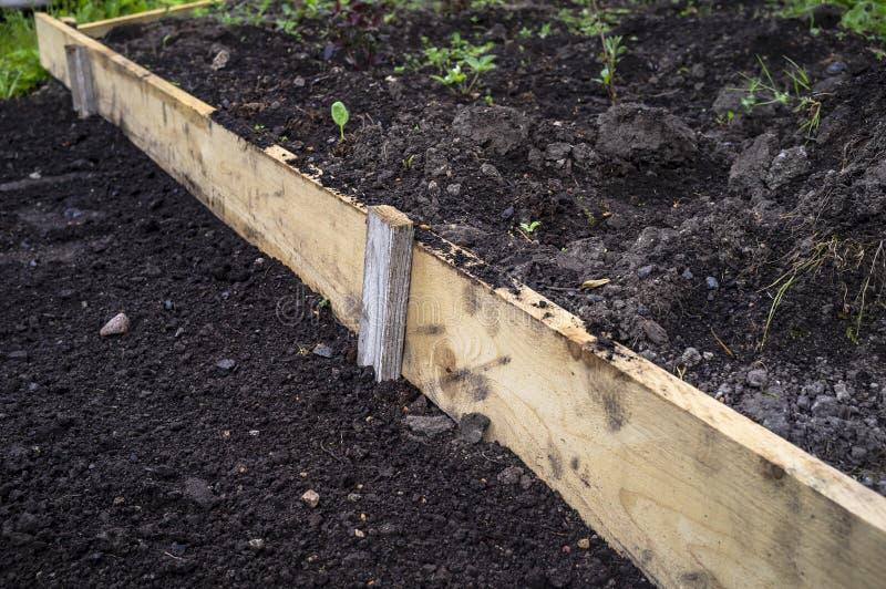 Lit de jardin clôturé avec la planche en bois, le jardin de campagne, une journée de printemps Préparation du sol pour planter de images libres de droits
