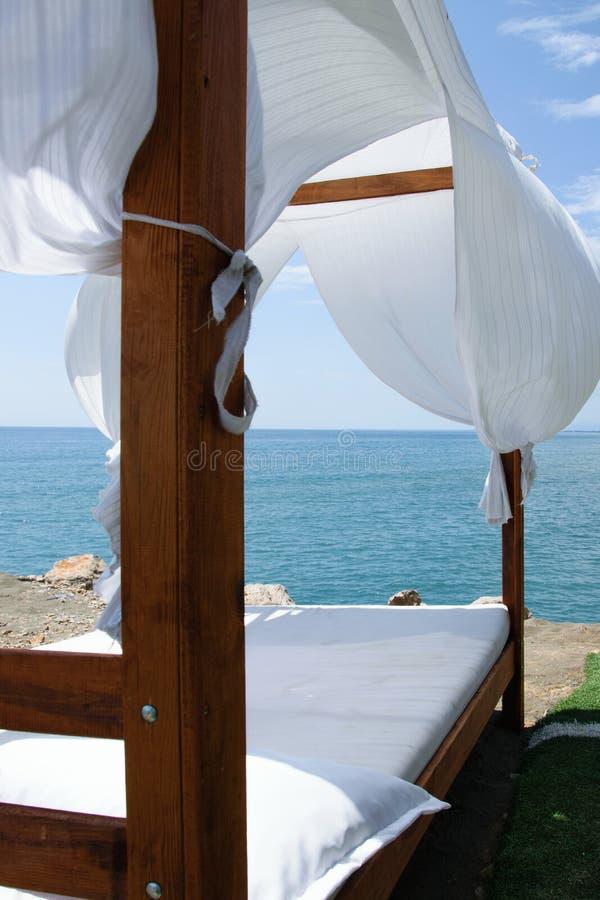 Lit de luxe et romantique sur le bord de la mer pendant des vacances de détente photos libres de droits