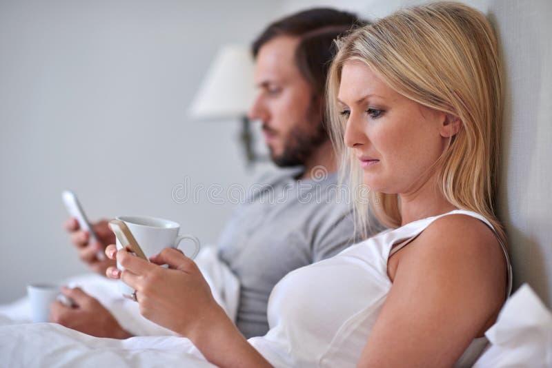 Lit de téléphone portable de couples photos libres de droits