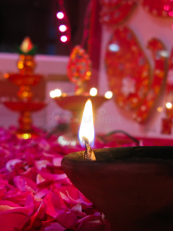 A lit diya on bed of roses. A lit baked mud diya on rose petals with items of worship in the background royalty free stock image