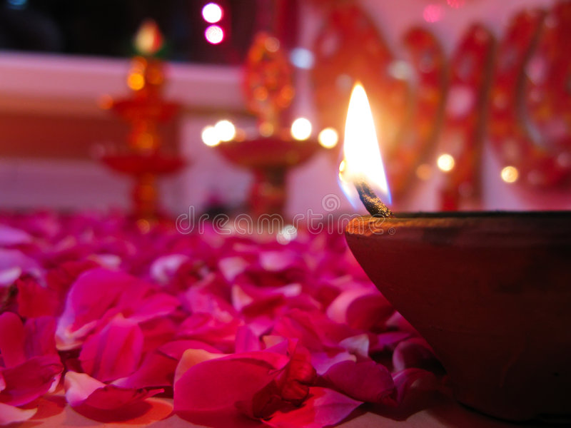 A lit diya on bed of roses. A lit baked mud diya on rose petals with items of worship in the background royalty free stock photography