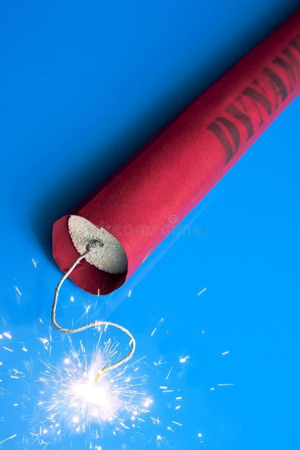 Lit dynamite stick on a blue background stock images