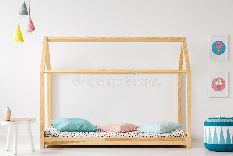 Lit en bois et en forme de maison pour un enfant, pouf, table, lampes et glace-c image stock