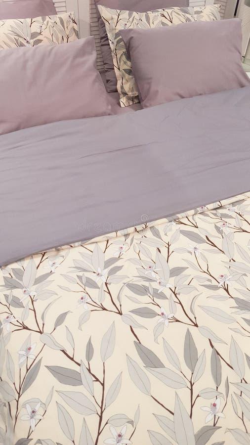 Lit et nightstand clairs avec l'usine de fleurs photographie stock